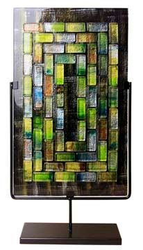 A tall, rectangular fused glass decorative panel featuring rectangular glass pieces in concentric patterns.  Stand included