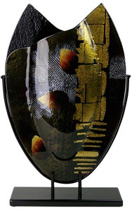 An oval, fused glass vase featuring browns, gold black, white, with some red and gold metallic hand painted details.