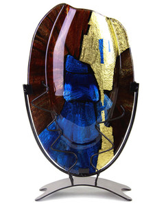 A 15 inch oval fused glass vase, from our Speedy series, featuring blue, brown and black, with metallic gold hand-painted details. Stand included