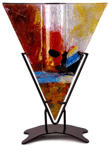 This triangular shape bud vase incorporates fused glass with red, blue, yellow gold and black.  In the Horizon series. Stand included