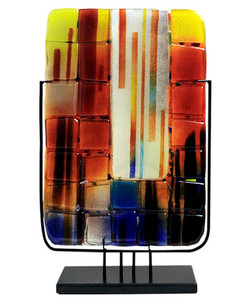 A tall, rectangular vase with square glass appliques applied and fused in place.  Blue, black, red, orange and yellow.  Stand included