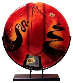 This 18-inch round fused glass platter features red, yellow and black along with some metal mesh appliques fused in place.  Stand included