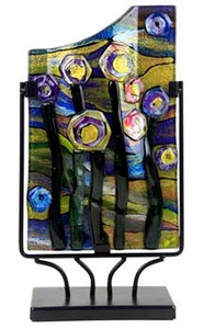 This 15-inch rectangular fused glass platter features primarily green and yellow, with touches of blue, violet and black with hints of pink.  Abstract flowers, reminiscent of a starry night.   Stand included
