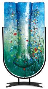 Marine colors are featured in this U-shaped fused glass vase with blue and green, along with many other colored pieces fused in place.  Stand included