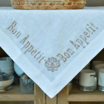 "Crown Linen White Table Topper with ""Bon Appetit"" Embroidery"