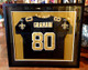Saints player Jimmy Graham jersey mounted on a gold mat with a black and white band around it.  This is our favorite way to frame  them.