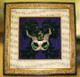 Mardi Gras Mask Shadowbox. It has an antique gold frame with black edging, textured cream mat with the sheet music to a Mardi Gras song drawn on it.  This musical mat mimics the design on the cream panels on the mask.  A gold fillet on the edge of the mat finishes the look.