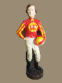 """Small Jockey 3  SKU # 20-2109  Indoors or out, this smart jockey in his beige breeches, red silks with yellow stripes and a yellow circle with the letters MP on the chest, and  a bow tie and matching hat would be a classic addition to any decor.  Cement.  18 lbs.  8 1/2""""W x 24""""H x 6""""D"""