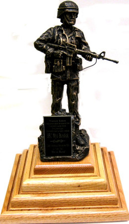 "9"" tall female warrior statue holding rifle mounted on a 9"" x 9"" x 4"" genuine oak coin display stand.  Total height is 13"".  Display stand can accomodate up to 9 each 2"" diameter coins per side and it is attached to a rotating base.  Also available with male statue, please specify.  Coins are not included."
