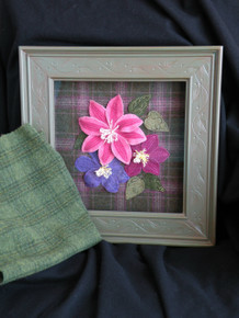 Current kit features the wool in the foreground as the background fabric.  Sorry, the pink plaid has long been sold out!  All the hand dyed wools for the flowers are the original colors/wools!