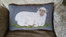 """Reposing Sheep"" hooked by designer, Kathy Gaul.  Off the bolt felted wools used to hook this pillow, sized 16"" x 10"", finished without the word ""Sheep"" at bottom.  Canvas IS drawn with wording option for finished size of 16"" x 12""."