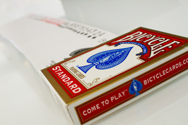 Red Bicycle Playing cards spread across a table with the tuck box. Bicycle playing cards available in Australia from http://shop.kardsgeek.com