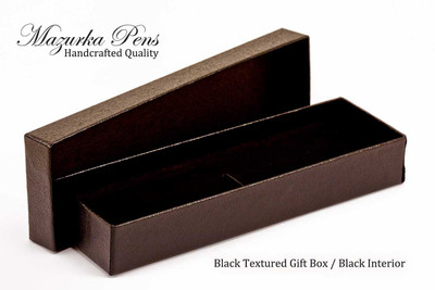 Black textured pen gift box made from rigid paperboard.  Has padded interior (black shown), strap and separate top.  Holds one pen (not included).  Shown open.