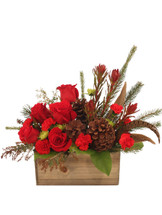 "4.5"" x 5"" x 10"" rectangular wooden planter box with liner wet floral foam foliage: salal, acacia (or sprigs of dried filler), Aussie pine (or other seasonal evergreens) 1 stem spray leucadendron (separated) 5 red roses 2 stems red mini carnations 1 stem green spray mums 3 natural pine cones on wooden picks 3 pheasant feathers"