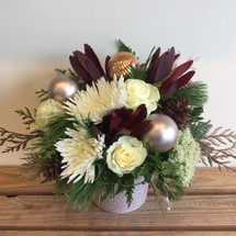 Winter Elegance at its best. Beautiful container filled with holiday greens, white roses, white spiders, leucadendron, and holiday balls