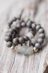 bundle of gray wooden bracelets with a mix of recycled glass beads