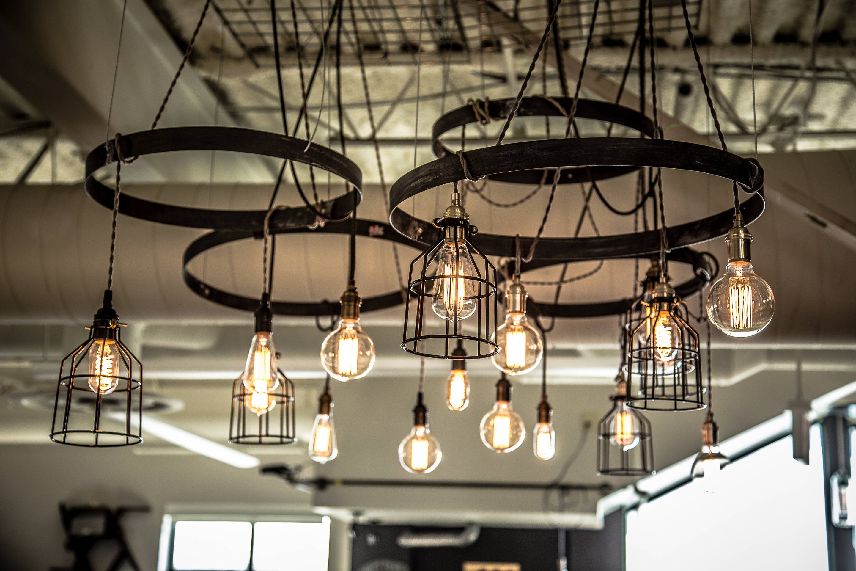 clypd-inc-office-space-in-somerville-ma-after-pic-16-pendants-hung-from-4-steel-hoops-mix-of-bulbs-and-cages-photos-by-nate-design-by-stephanie-6.jpg