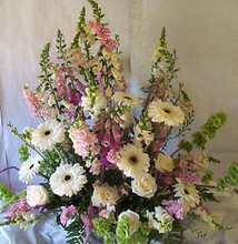 Fresh flowers in soft hues arranged in a wicker basket.