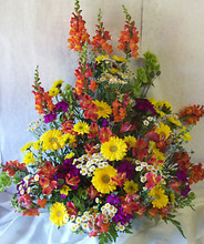 Fresh flowers in bold hues arranged in a wicker basket.