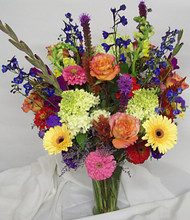 Bright mix of fresh flowers arranged in a trumpet vase.