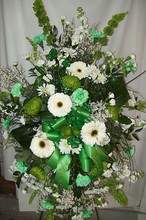 Standing funeral spray of green and white fresh flowers and green ribbon.
