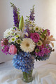Trumpet vase filled with hydrangea, roses, gerberas, lilies, and larkspur.
