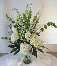 Elegant calla lilies, hydrangea and bells of Ireland in a stylized format.