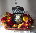 Basket of Autumn fresh flowers surrounding a keepsake lantern.