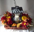 Basket of Autumn fresh flowers surrounding a keepsake lantern.