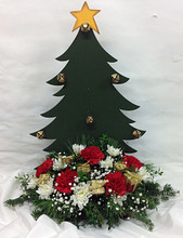 Wooden Christmas tree adorned with jingle bells, fresh holiday greens and flowers, and ornaments.