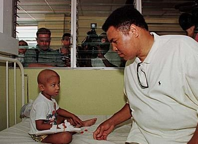 Ali visits with a sick child in a hospital