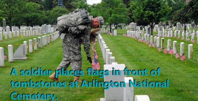 A soldier adorns tombstones with American flags at Arlington National Cemetery
