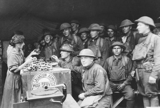 A doughnut girl distributes donuts to soldiers during World War I