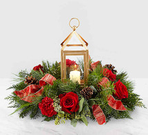 The Beautifully Bright Centerpiece draws in the attention of the room while perfectly accenting the holiday festivities. An array of red roses, red carnations, seeded eucalyptus and Christmas greens make up a truly wonderful arrangement. Whether it's a gift for you or someone else, this piece clearly belongs in the center of the room. A candle shines within the glass insert surrounded by a matte gold metal lantern.