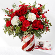 FTD proudly presents the Better Homes & Gardens Holiday Wishes Bouquet. Come home for the holidays with this simply stunning fresh flower bouquet. Rich red roses and mini carnations create a splash of Christmas color accented with white carnations, berry pics, and fragrant holiday greens. Presented in a red and white striped candy cane inspired shining ceramic vase tied at the top with a natural rope accent to give it that down home feel, this gorgeous holiday bouquet is ready to send your warmest wishes to friends and family throughout the yuletide season