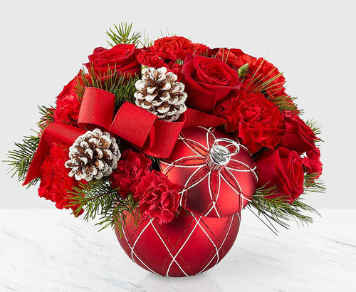 Deck the halls, and their holiday home with a bouquet that shares the most beautiful season's greetings. Bright red roses, red carnations and Christmas greens come together within an ornament vase with stem lid to create our Making Spirits Bright Bouquet. Featuring a bold red ribbon and natural pinecone pics, this arrangement captures the joy of holiday magic for whoever it's given to.