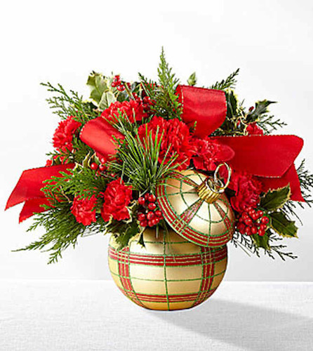 The FTD Holiday Delights Bouquet sparkles with the magic and enchantment of the Christmas season to send your warmest yuletide wishes to every person on your holiday shopping list. A bold mix of red blooms, including roses, carnations, and mini carnations, are sweetly set amongst variegated holly and fragrant holiday green accents to create an elegant holiday display. Presented in an ornament inspired gold, red, and green plaid keepsake ceramic vase, intended to become a treasured holiday accent piece for years to come