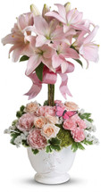 Like springtime in Paris, this flirtatious topiary makes romance bloom! She'll adore the pale pink lilies, a pretty pink ribbon, and charming french country pot as well as the loving sentiment that comes with it!