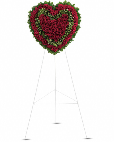 Remember a loved one's generous heart with this red arrangement in a classic heart shape, a declaration of eternal love and devotion. Speak from your heart. This majestic funeral display is a charming, heartfelt way to express your love, composed of sympathy red roses and carnations with variegated pittosporum and ming fern.  Red carnations, red roses, variegated pittosporum and ming fern are arranged into a touching heart design that's presented on a wire easel.