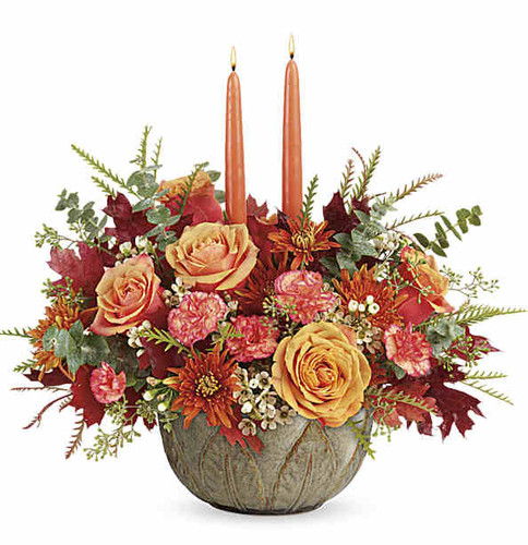 Warm their hearts and brighten their table with this lush fall rose centerpiece, arranged in a hand-glazed, oven-to-table stoneware serving bowl they'll enjoy for many years to come!  Light orange roses, orange miniature carnations, and bronze cushion spray chrysanthemums are accented with white waxflower, spiral eucalyptus, grevillea, seeded eucalyptus, brown transparent oak leaves, and two peach candles.  Delivered in Teleflora's Artisanal Autumn Bowl or Similar.  Orientation: All-Around