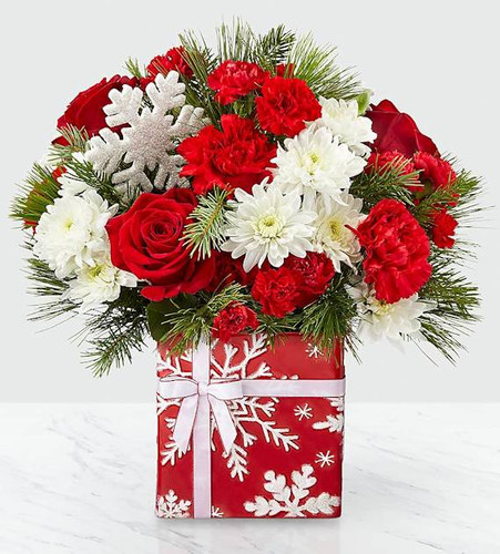 Delight your loved ones with a gift that is handcrafted for just for them. Our Gift of Joy Bouquet features red roses, white cushion pompon and red carnations set in a red vase with shimmering snowflake detail, ribbon accent and completed with a shining snowflake pic. Perfect for host to help decorate their holiday home or a close friend to share festive wishes, there is no better bouquet to give during the yuletide season.