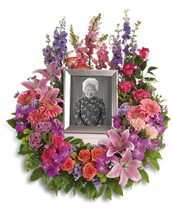 Keep fond memories close to your heart with this lovely feminine floral wreath. It's perfect to surround a framed photo of the departed. Includes a multitude of flowers such as roses and carnations, along with pink gerberas, oriental lilies and snapdragons, purple orchids and asters, plus lavender delphinium. Green button spray chrysanthemums provide beautiful accents.  Please note: Arrangement does not include picture frame.  May be placed on a table or a standing easel.