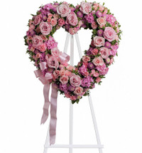 In the shape of a heart, and accented with a pink satin ribbon, this garden of delicate blooms is a tender and classic tribute to a precious life, and a cherished expression of love and sympathy.  Beautiful flowers such as light pink roses, hydrangea and miniature carnations mix with lavender chrysanthemums on an open heart-shaped wreath.