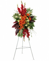 While the loved one is no longer present, there are happy times that will never be forgotten. This radiant spray of red and orange flowers will be a lovely reminder.  The stunning arrangement includes orange Asiatic lilies, red gladioli, green carnations, peach hypericum, emerald palm and red ti leaves, accented with assorted greenery.