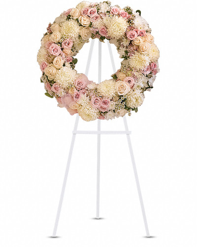 A pure and delicate expression of adoration. Accented with a sheer pink organza bow, this wreath of white, crème, and pale pink petals gently embraces loving memories, and offers solace and sweet thoughts at a time of loss  Lovely blooms such as cream and pink roses, pink hydrangea and white chrysanthemums are nestled together and accented with organza ribbon. A touching and feminine wreath, ideal for a memorial service.