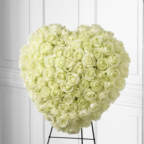 """The FTD® Elegant Remembrance™ Standing Heart is an exquisite display of peace and love. 77 Stems of white roses are artfully arranged in the shape of a heart and presented on a wire easel, creating a simply beautiful tribute for their final farewell service. Approximately 24""""H x 22""""W."""