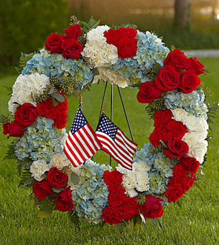 """Pay tribute to a life lived in devotion and service to country with a red, white and blue floral wreath embellished with the beloved stars and stripes. A fitting way to celebrate the life of a veteran, government worker or any American patriot, this beautiful, full ring of colorful flowers includes red roses, red and white carnations and blue hydrangeas, beautifully complemented by lush greens. It adds a tasteful salute of patriotism on a floor-standing easel at a wake, for funeral services and for graveside burial services. Approximately 28""""H x 24""""W."""
