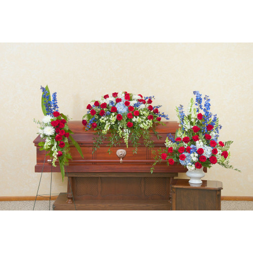 Honor Remembrance Trio, a Casket spray and 2 side pieces feature Roses, Hydrangea, Snapdragons, Delphinium in Reds, Whites, and Blues.