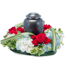 "Red, White and Blue blooms surround the urn of your loved one to show honor. Approximately 16"" (W) x 6""(H)"