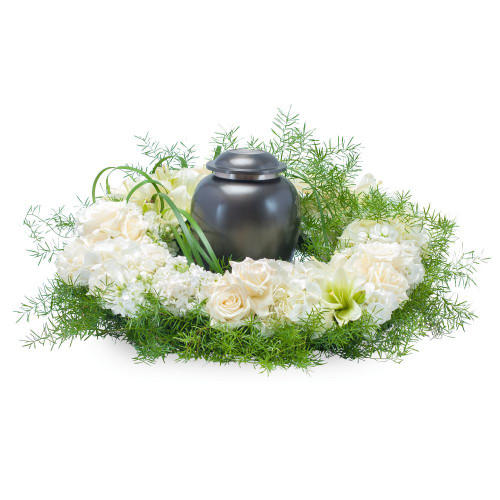 """White and cream blooms surround the urn of your loved one. Approximately 20"""" (W) x 6""""(H)"""